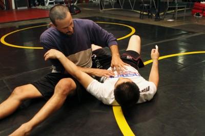 【写真】ホールディングダウン(抑え込み)の際の重心を置く位置を植松直哉に指導するリコ・チャッパレリ(C)MMAPLANET