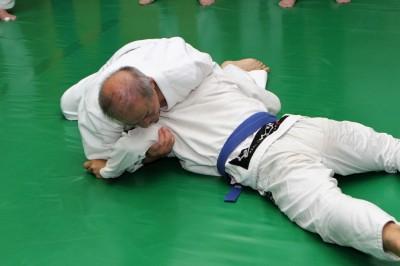 左肩や左胸を使って、相手の背中の上の部分にプレッシャーをかけて片手絞めにいく選択もある