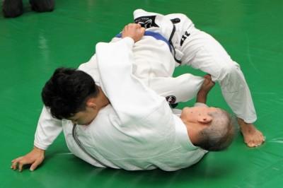 その手を引き上げ、右手はヒジをマットに立てて相手の左ヒジを押し上げる。と同時に左足で、相手の右足の付け根を跳ね上げる