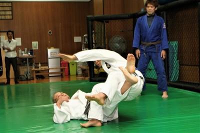 右足をしっかりと相手の両足のヒザ裏に当てて、左足は腰の位置に当てて自らの両足を交錯させるように、相手の両足を刈り