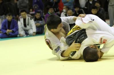 2013年12月のブルテリア・オープンで、ジョアオにバックを取られそうになる塚田